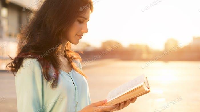 Student Mädchen lesen Buch im freien, genießen Sonnenuntergang