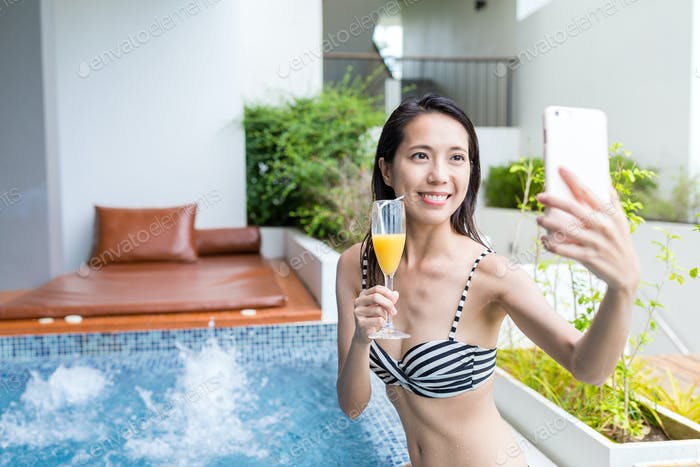 Woman taking selfie by mobile phone in jacuzzi spa