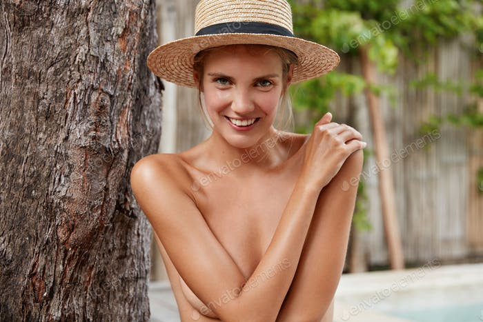 Waist up portrait of nude female wears only straw hat on head, covers body with hands, enjoys recrea