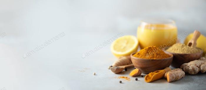 Gesunder veganer Kurkuma Latte oder goldene Milch, Kurkuma Wurzel, Ingwerpulver, schwarzer Pfeffer über grau