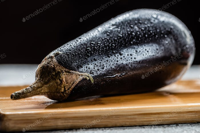 fresh ripe eggplant with water drops on wooden board isolated on black