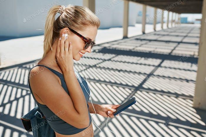 Молодая фитнес блондинка женщина в спортивной одежде, слушая музыку с ним
