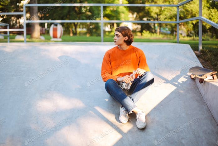 Young guy in orange pullover and jeans holding bottle of water i