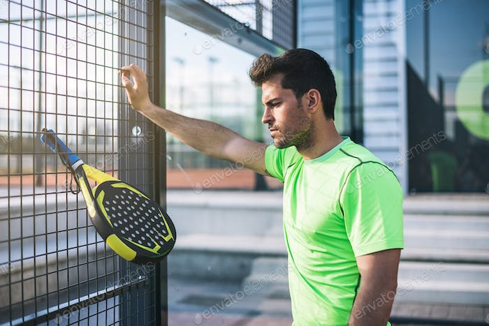 Sportsman resting from playing padel