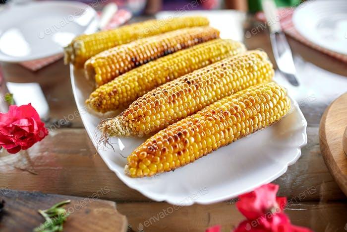 Gegrillte Maiskolben auf Teller auf dem Esstisch, Vorspeisen
