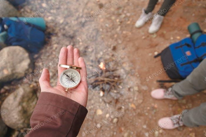 Un Hombre tiene una brújula en la Mano, de pie en una Playa de piedra