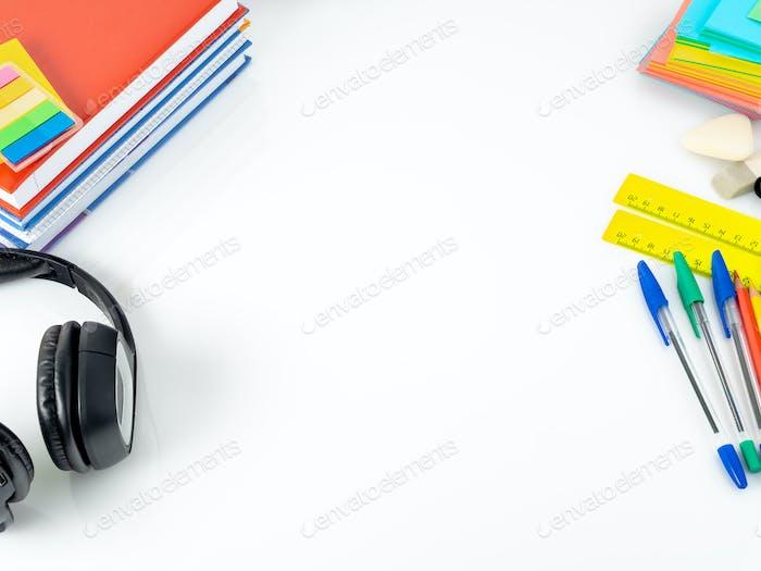 Kopfhörer und Schulbedarf auf weißem Tisch. Seitenansicht, leerer Raum. Zurück zum Schulkonzept.
