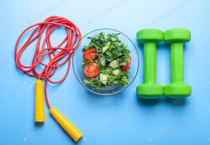 fresh salad bowl, dumbbells and jumping rope