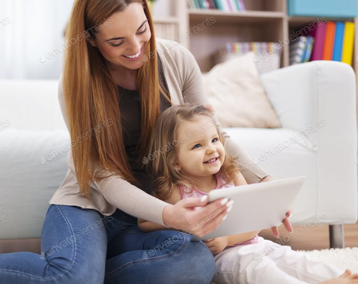 Mother and daughter have fun during the using digital tablet