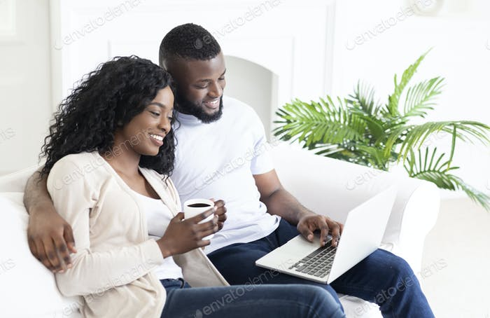 Young african american family browsing internet on laptop at home
