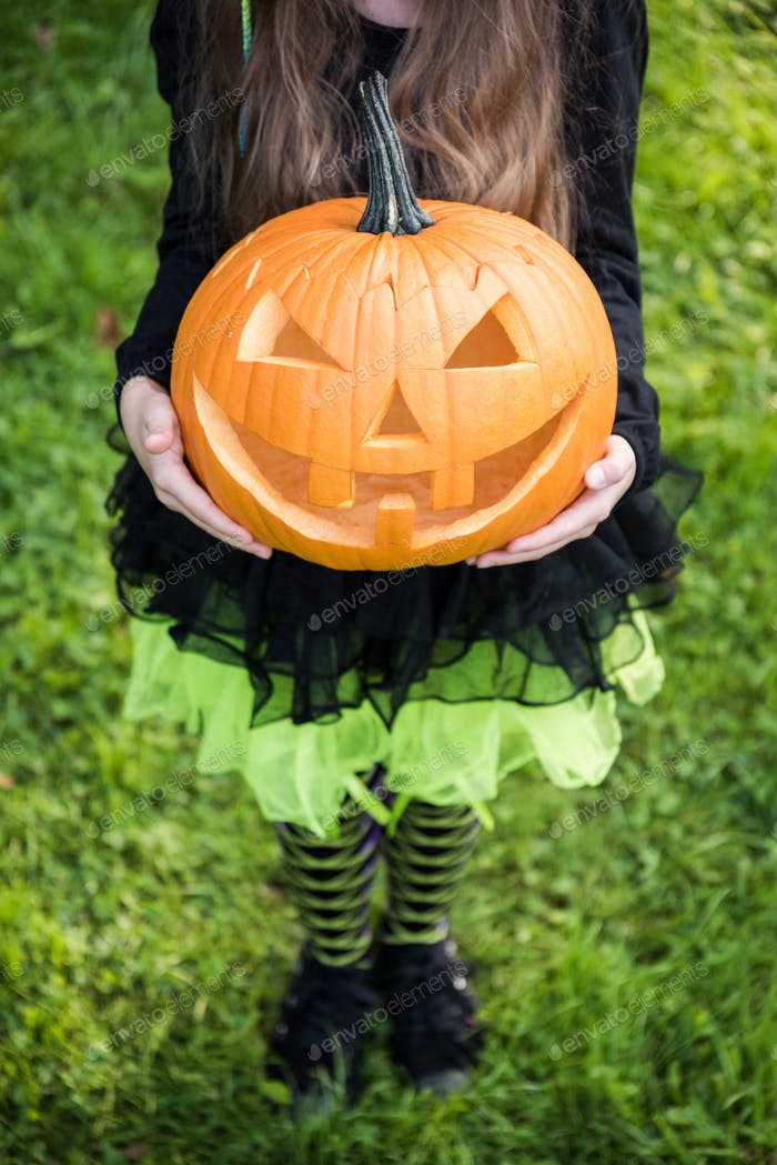 Girl in halloween costume holding spooky pumpkin