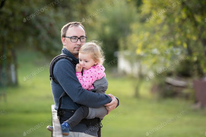 Father with his daughter in baby carrier. Green nature.