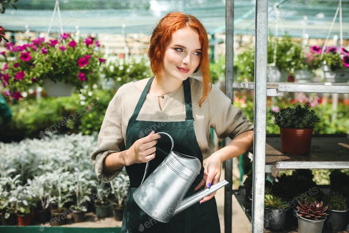 Beautiful smiling florist in apron standing with watering can in hands and  dreamily looking aside