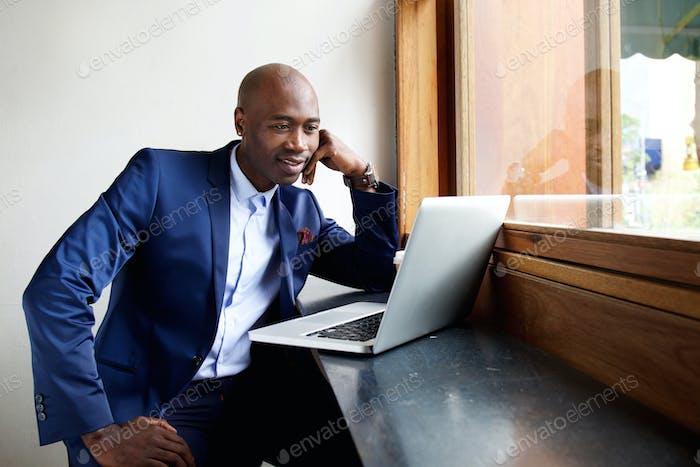 Geschäftsmann in einem Café mit Blick auf Laptop