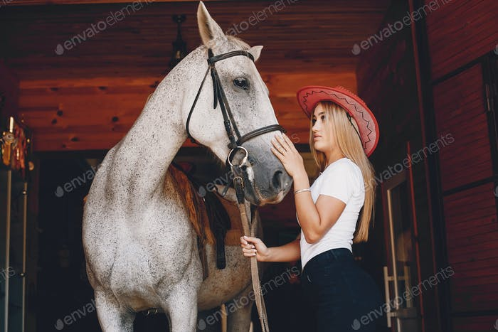 Elegant girl in a farm wiith a horse