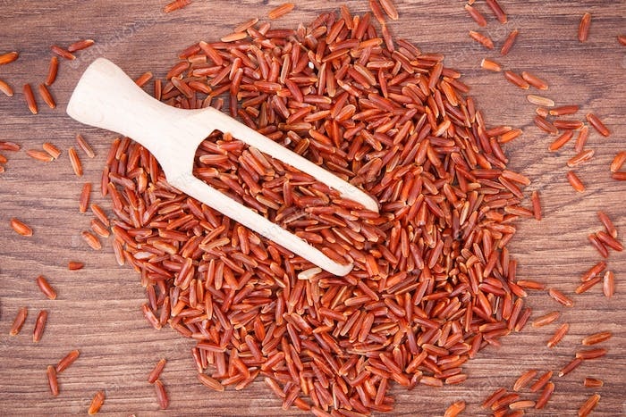 Heap of red rice with scoop, healthy nutrition