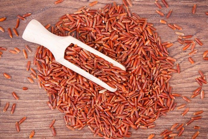 Haufen roter Reis mit Schaufel, gesunde Ernährung
