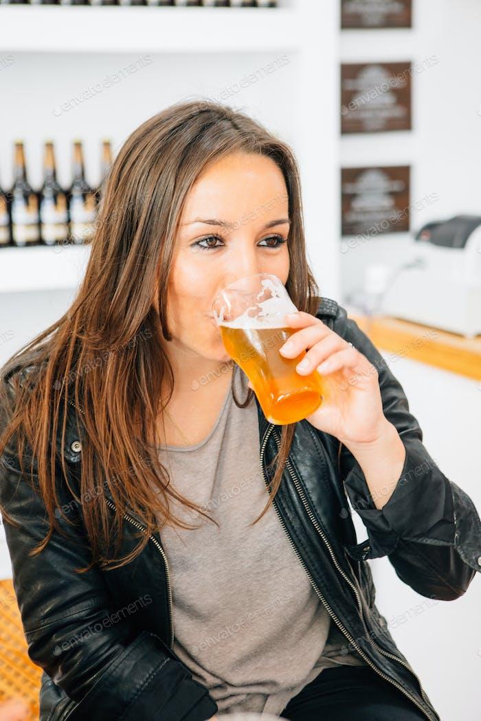 Beautiful brunette drinking light craft beer