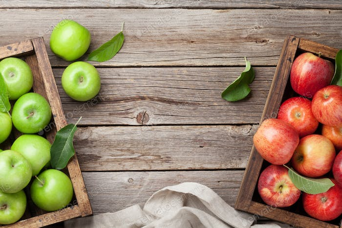 Green and red apples in wooden box
