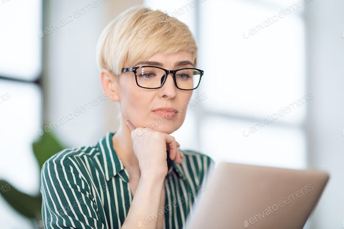 Entrepreneur Lady Using Tablet Reading News Sitting At Workplace Indoor