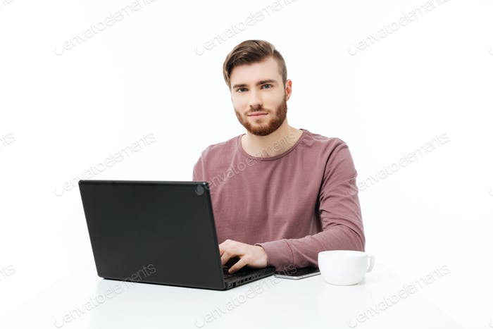 Handsome young man at the table looking in the camera working at the laptop computer isolated