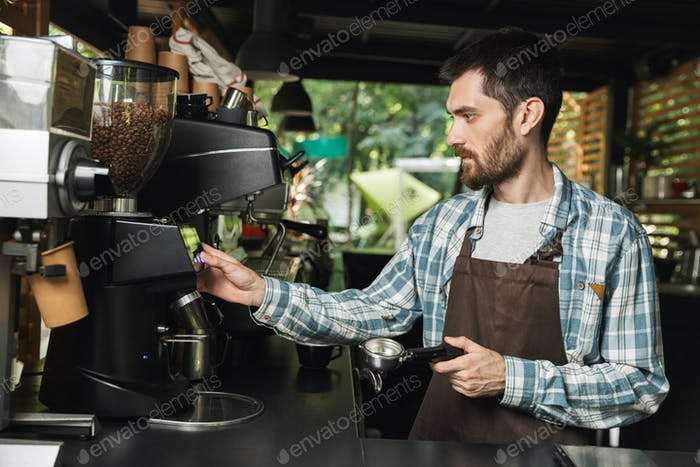 Portrait of serious barista man making coffee while working in s