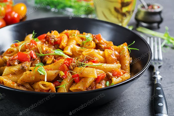 Penne pasta in tomato sauce with meat, tomatoes decorated with pea sprouts on a dark table.