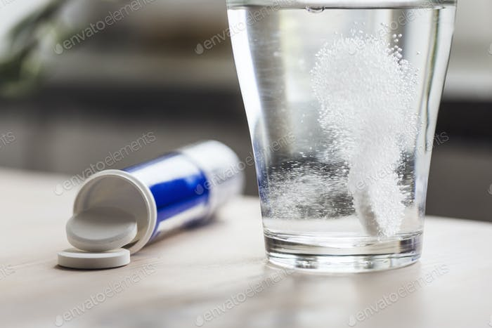 Close-up of glass of water and medicine on table