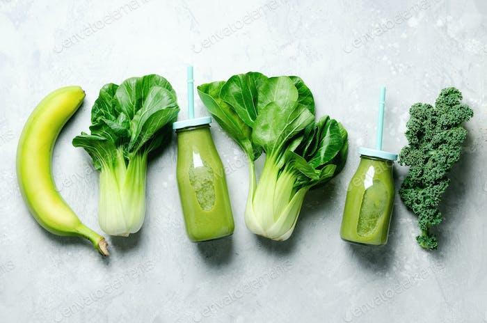 Grüner Smoothie im Glas mit frischem Bio-Gemüse und Früchten auf grauem Hintergrund