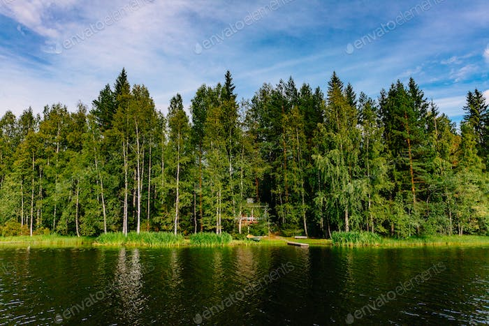 Idyllic countryside landscape view with blue lake and house on the shore. Summer cottage in Finland.