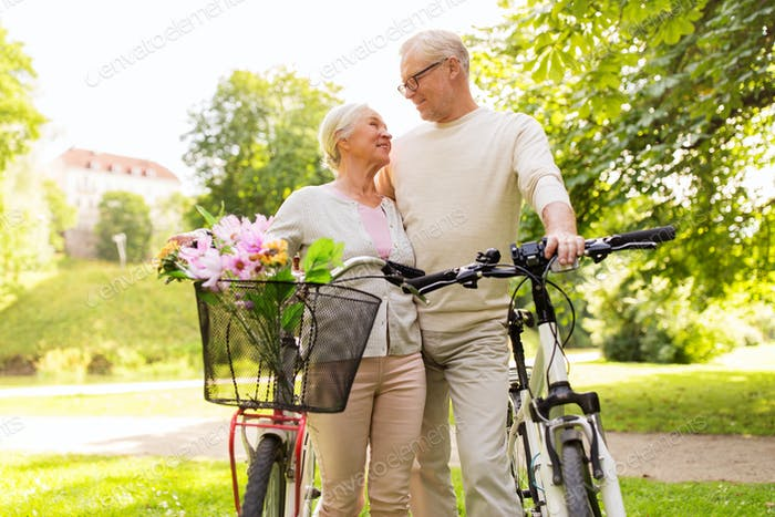 happy senior couple with bicycles at summer park
