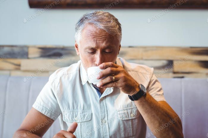 Casual man enjoying a cup of coffee at the cafe