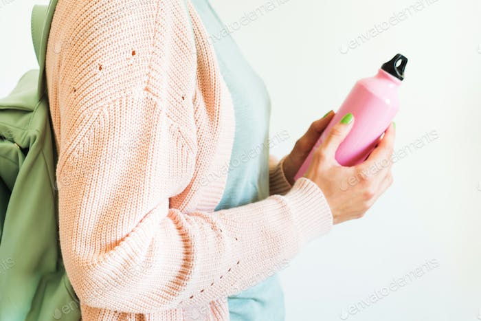Woman holding pink reusable water bottle