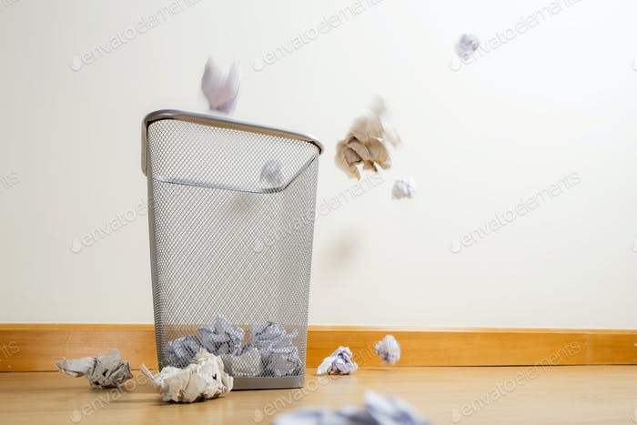 Silver trash bin and crumpled papers
