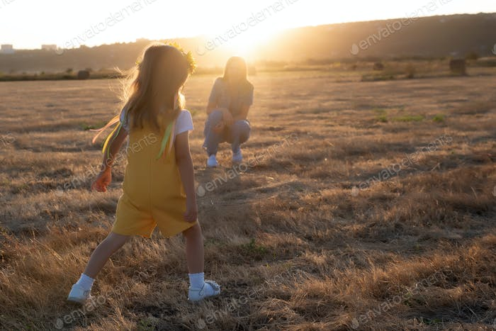 Happy girl child in yellow dress runs to her mom in autumn field