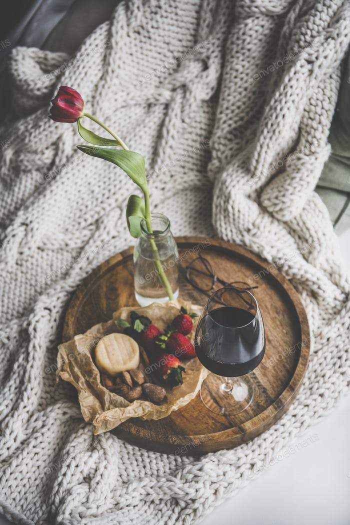 Glass of red wine, different snacks and tulip in jar