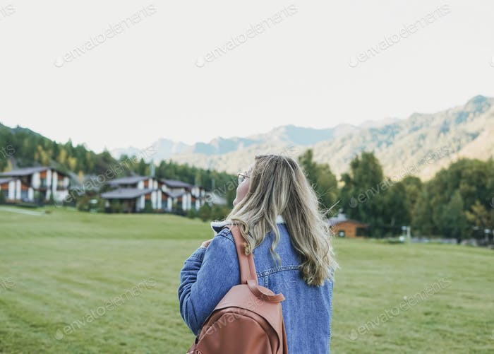Young woman in jeans coat at cottage village on mountains region