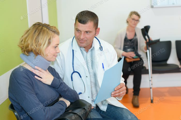 pleasant smiling doctor talking with his patient in waiting room