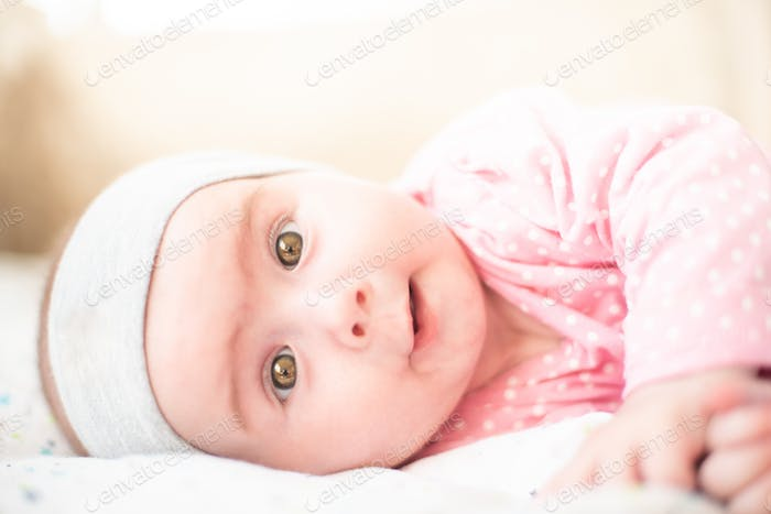 Adorable baby girl in pink lie on side and looking towards camera and smiling. Health concept