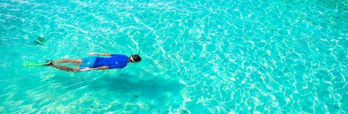 Junge schnorcheln im tropischen türkisfarbenen Ozean