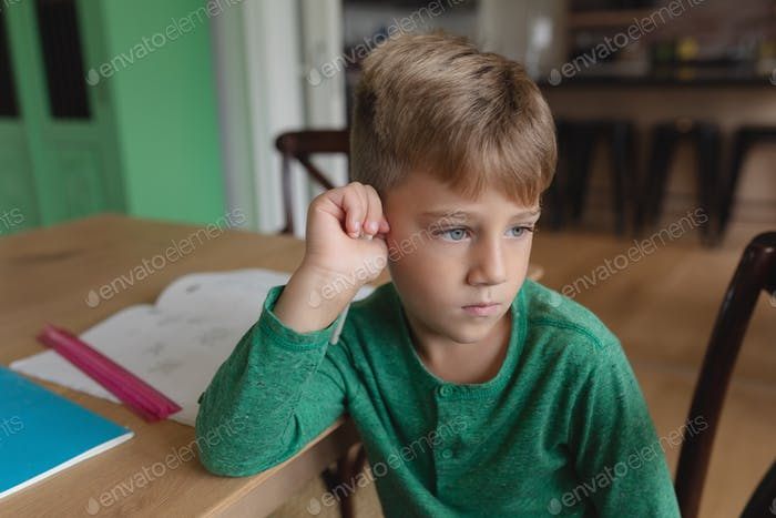 Front view of cute Caucasian boy looking away while sitting on dining table in a comfortable home