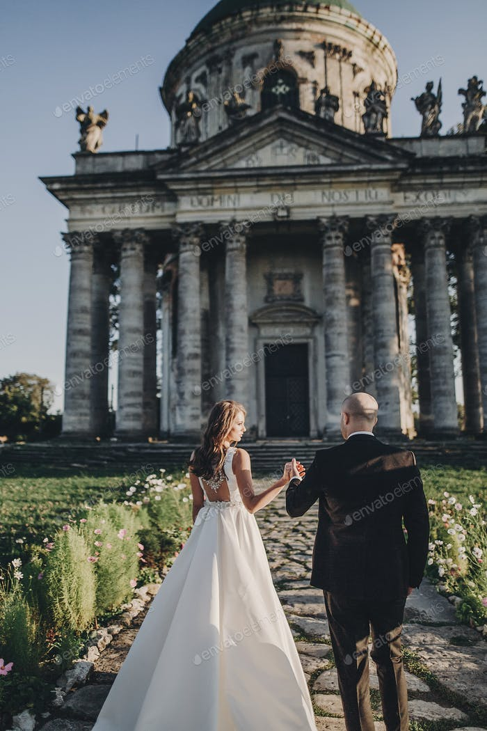 Bride and groom posing on background of ancient columns and nature