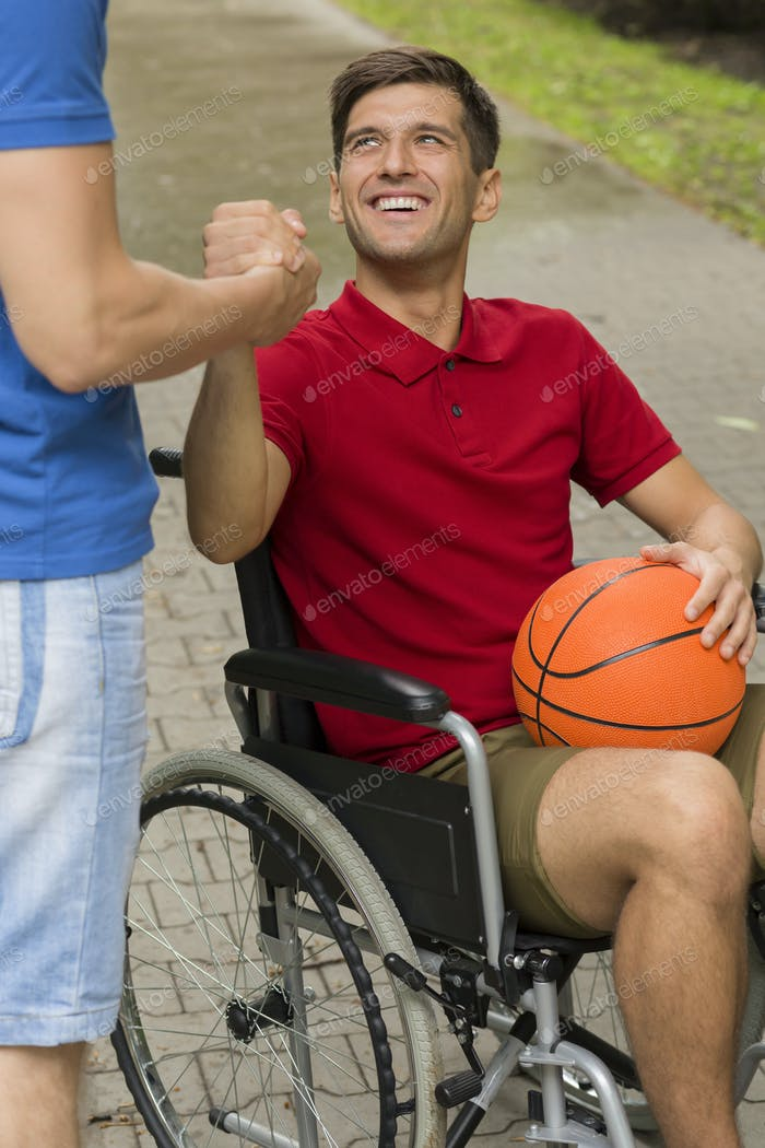 Alegre Hombre discapacitado sosteniendo un baloncesto