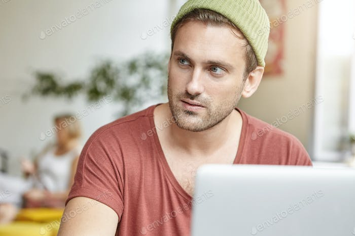 Handsome young male copywriter working remotely on portable web enabled electronic device, having pe