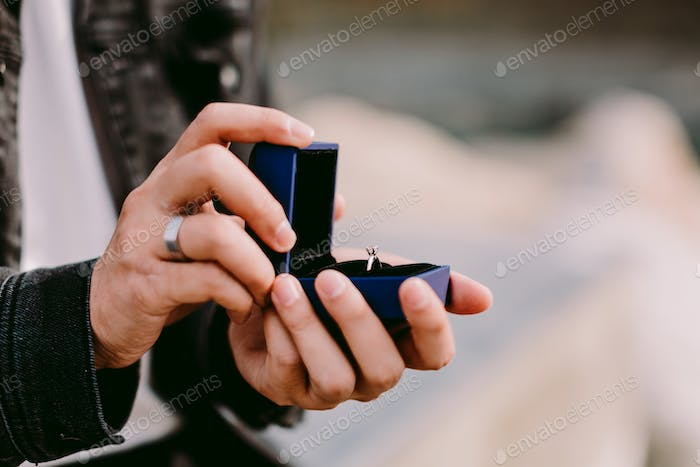 man holding engagement ring in box for proposal