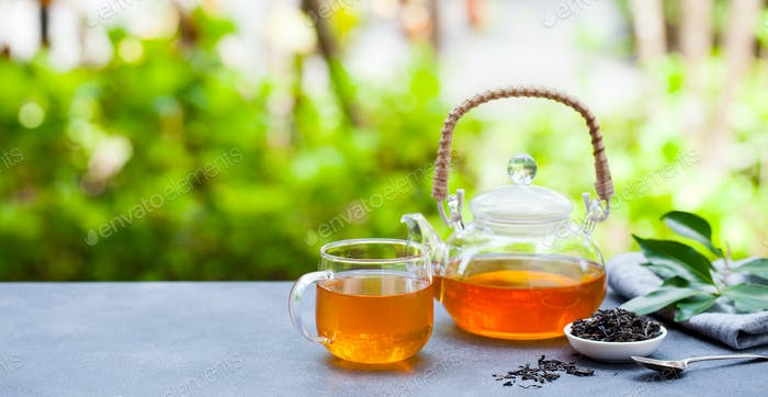 Tea in Glass Cup and Teapot on Summer Outdoor Background. Copy Space.