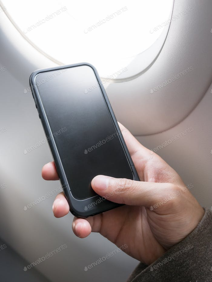 Hand holding cell phone on airplane
