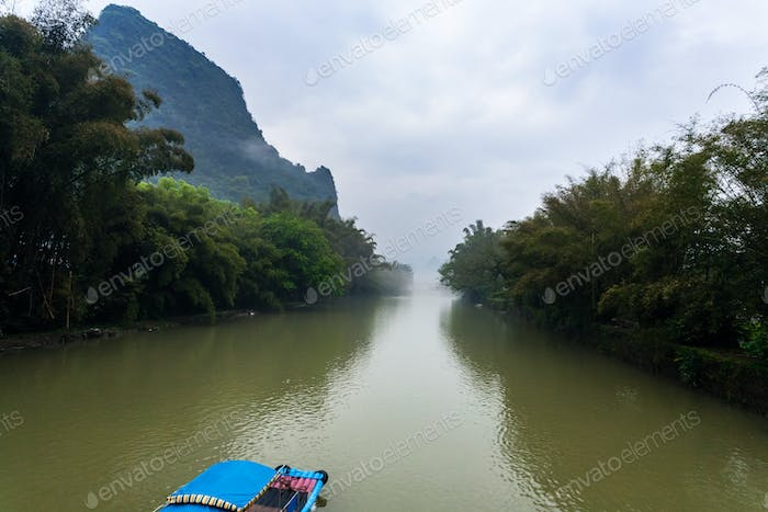 chinese boat on river near peaks near Xingping