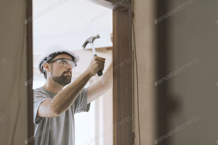 Carpenter installing a door jamb at home