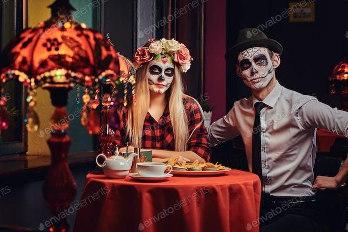 Молодая привлекательная пара с нежитью макияж ест начос во время свиданий в мексиканском ресторане.